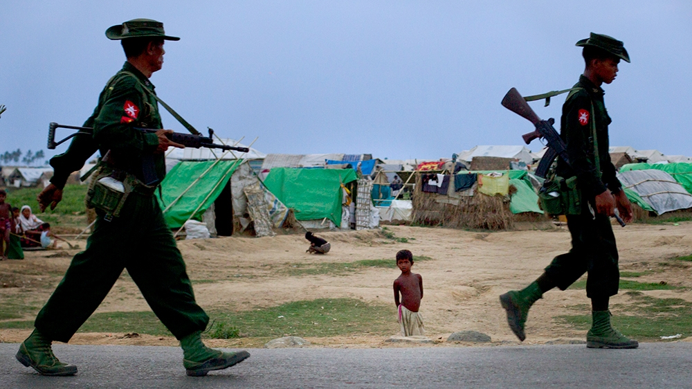 In this May 13' 2013 photo, an internally displaced Rohingya boy, center watches army soldiers on foot-patrol in the foreground of makeshift tent camps for Rohingya people in Sittwe, northwestern Rak