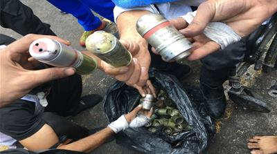 Protesters hold tear gas canisters