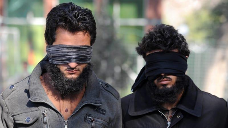 Afghan security officers escort two alleged ISIL members in Nangarhar province, Afghanistan [EPA]