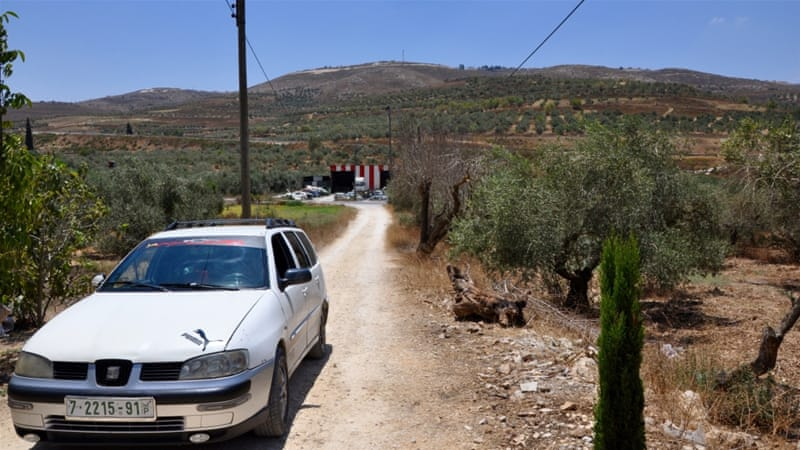 Part of an outpost extending from Yitzhar can be seen from the road passing by Nimer Tirawi's home in Burin [Emily Mulder/Al Jazeera]