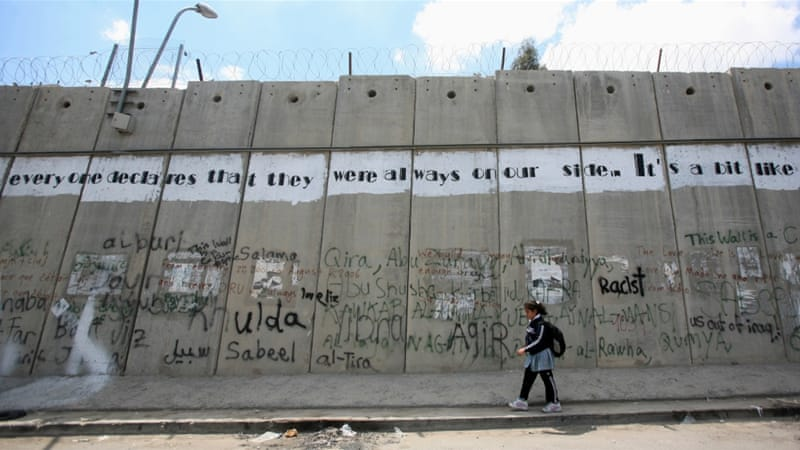 A Palestinian girl walks past graffiti on the controversial Israeli 'security' barrier in the West Bank, April 2009 [Fadi Arouri/Reuters]