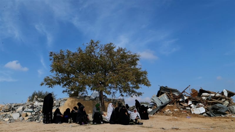 Women sit next to ruins from their homes, which were demolished by Israeli bulldozers in Umm Al-Hiran, a Bedouin village in southern Negev Desert, on January 18 [Ammar Awad/Reuters]
