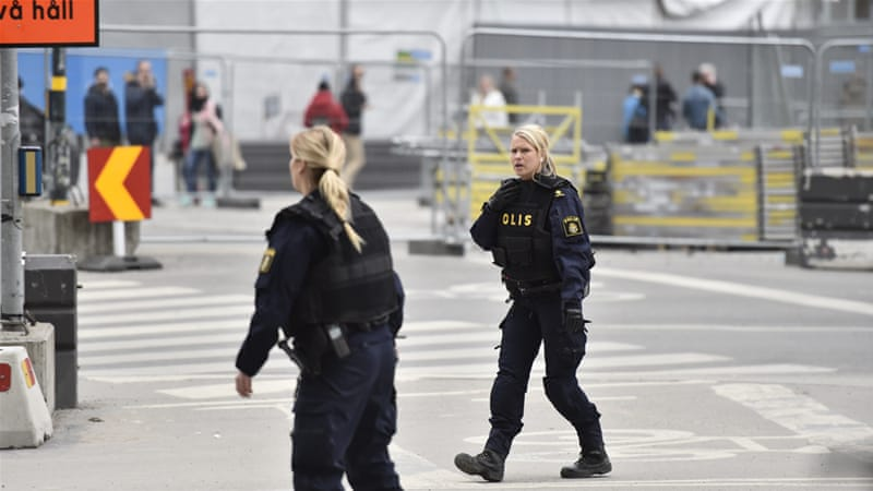 Swedish police officers guard the area after the truck crashed into the department store [Noella Johansson/EPA]