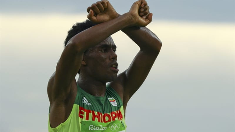 Feyisa Lilesa of Ethiopia crosses his wrists in solidarity with the Oromo people after crossing the finish line at the 2016 Rio Olympics [Reuters/Athit Perawongmetha]