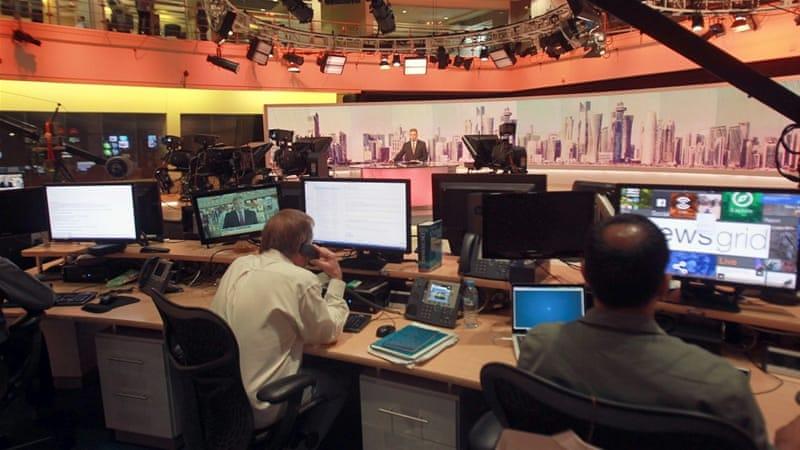 Al Jazeera staff work inside the network's headquarters in the capital Doha on June 8 [Naseem Zeitoon/Reuters]