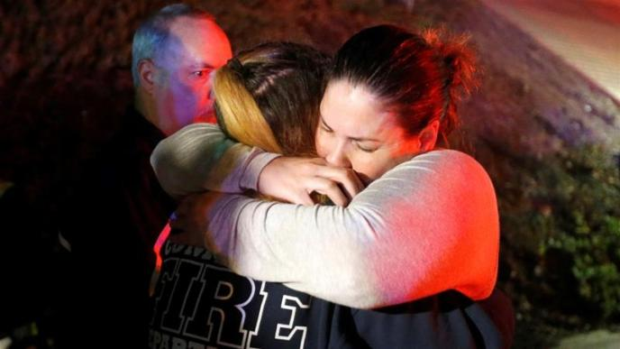 People comfort each other after a mass shooting at a bar in Thousand Oaks, California [Ringo Chiu/Reuters]
