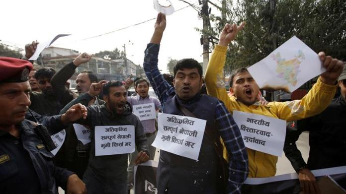 Nepalese students burn a map of India near the Indian embassy during a protest in Kathmandu against the new map of India [Navesh Chitrakar/Reuters]