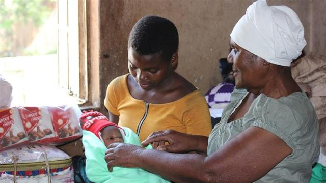 New mother Vimbai Mhere gave birth to her daughter in a 'back yard' clinic run by midwife Esther Zinyoro [File: Chris Muronzi/Al Jazeera]