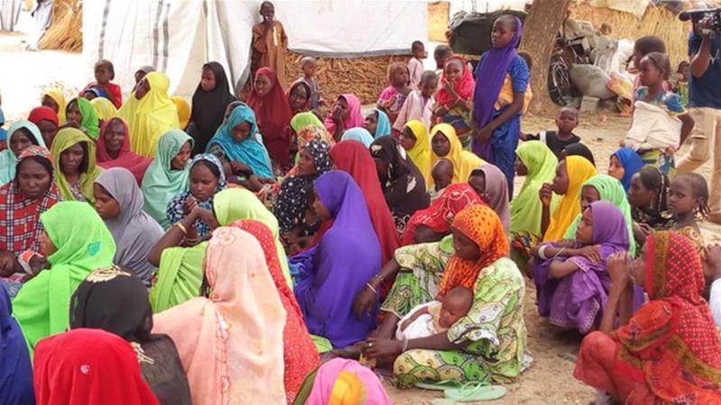 Mulheres e crianças se reúnem no campo de deslocados internos de Madinatu para ouvir os membros da Coalizão Comunitária Borno falar sobre os perigos do tráfico de pessoas [Philip Obaji Jr / Al Jazeera]