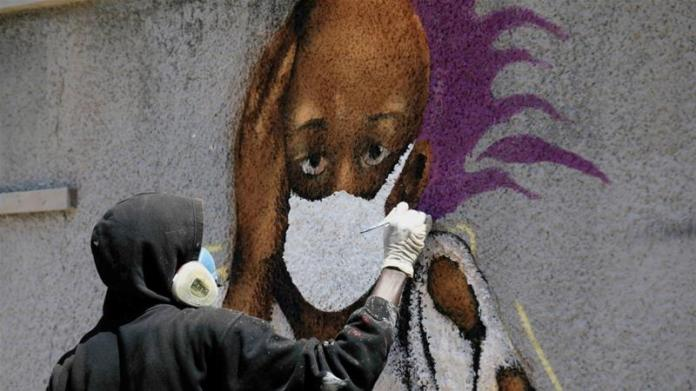 Serigne 'Zeus' Boye, a graffiti artist, works on his mural to encourage people to protect themselves amid the COVID-19 outbreak in Dakar, Senegal on March 25, 2020 [File: Zohra Bensemra/Reuters]