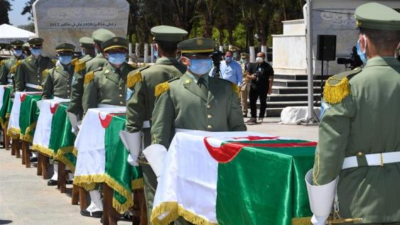 Republican Guard troops stand with 24 coffins during a ceremony to lay to rest the remains of resistance fighters [Algerian Presidency Press Office/AFP]