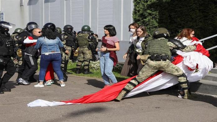 Officer detain protesters with a historical white-red-white flag of Belarus during a rally against police brutality on Sunday [Tut.By via Reuters]