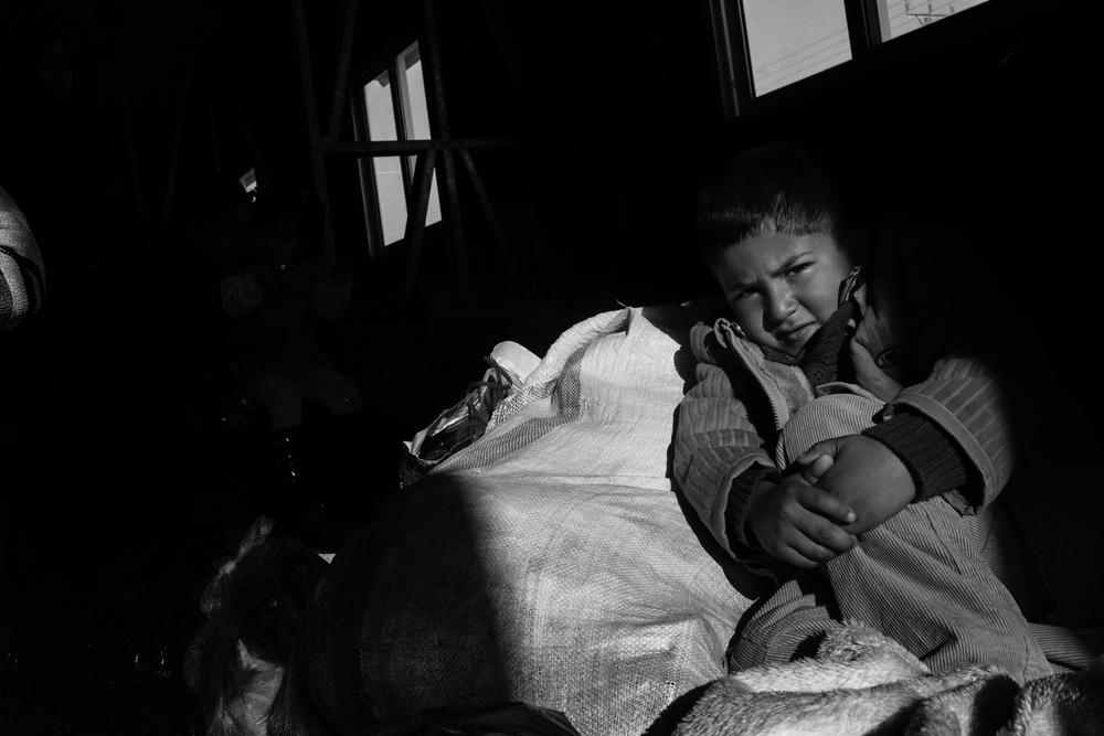 Mohammed arrived from Homs. He sits on a bag of winter clothing, the only belongings his family has.