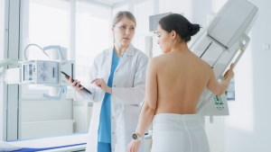 patient and physician discussing mammogram by the machine