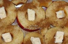 Puneti rondelele de mere la baza vasului in care veti introduce friptura de porc la cuptor (eu am folosit un vas de yena), astfel incat sa acoperiti toata suprafata acestuia cu felii de mar. In mijlocul fiecarei bucati de mar (locul ramas gol dupa extragerea cotorului) puneti cate 1 lingurita de zahar brun, mai apoi presarati pe deasupra merelor un pic de scortisoara macinata, dupa care, la final, puneti cate un cubulet de unt in mijlocul fiecarui rondel de mar.