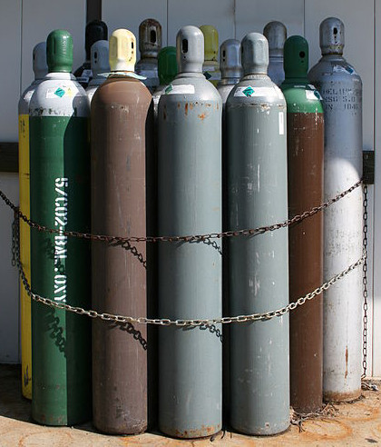 An assortment of compressed gas tanks chained to a wall.