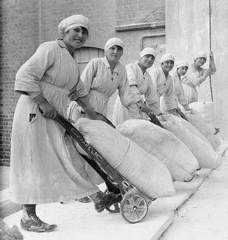 Female workers pose with trolleys laden with sacks of flour in the grounds of the mills of Rank and Sons, Birkenhead, Cheshire, in September 1918.