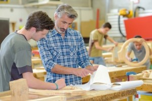 Teacher helping student in woodwork class
