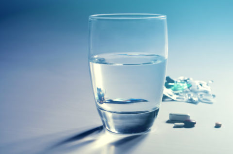 A half-full glass of water and a few pills next to it.