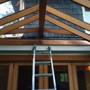 Narrow custom copper gutter mimics wood beams, catches water in very narrow gap between beams and ceramic tile roof. Seattle All About Gutters