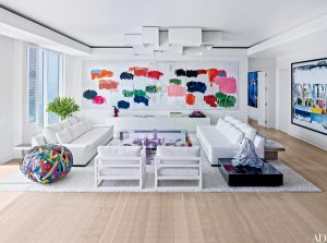 modern white room with large white abstract canvas painting on wall with pink,red,blue and green paint drips
