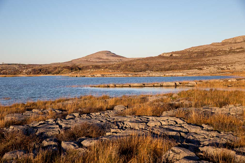 Lake Gealain in the golden evening light with the unusual rocky mountains of the burren in the background