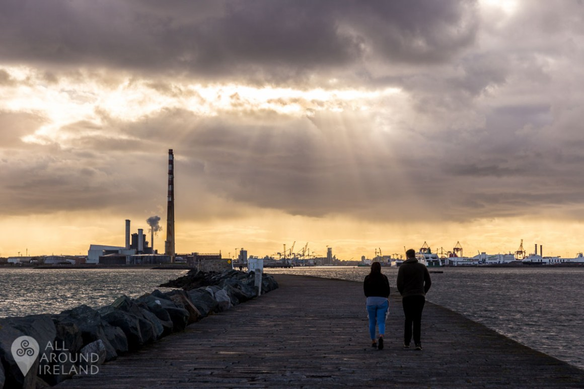 A couple walk back towards the city as rays of light break through the clouds over the Poolbeg Chimneys
