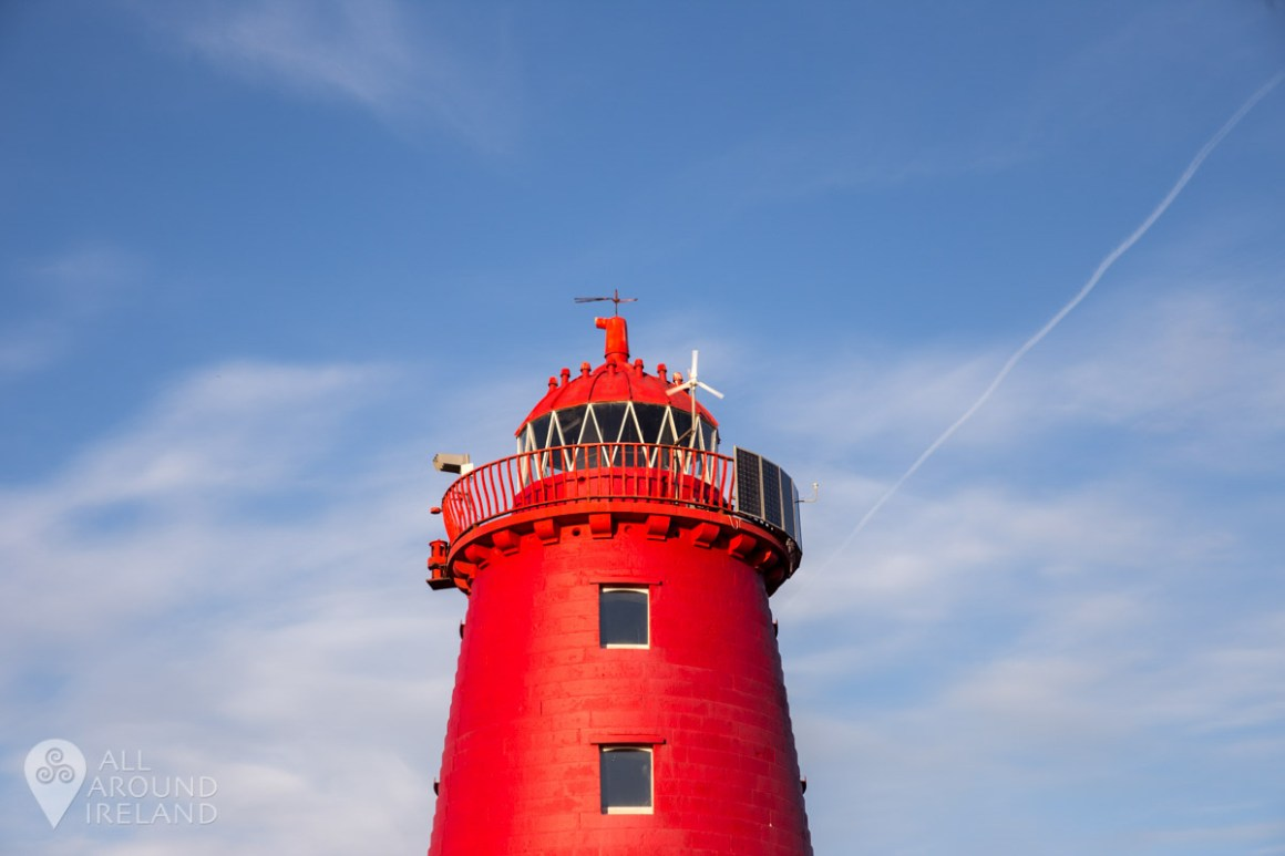 The bright red lighthouse stands out against a blue sky