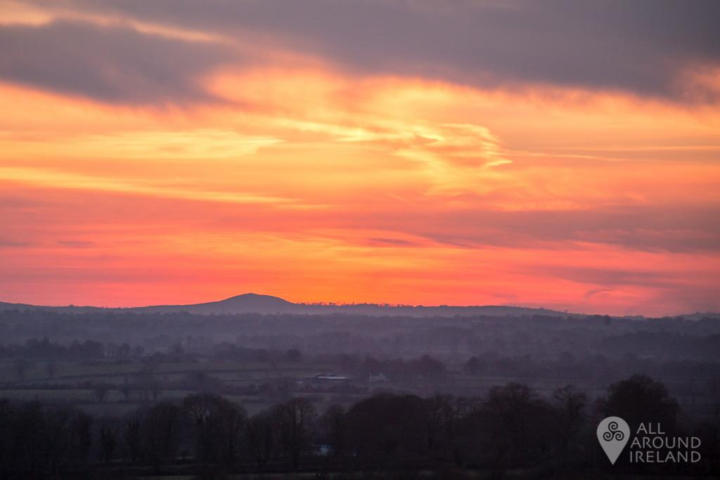 A red sky as the sun dips below the horizon near the Rock of Cashel