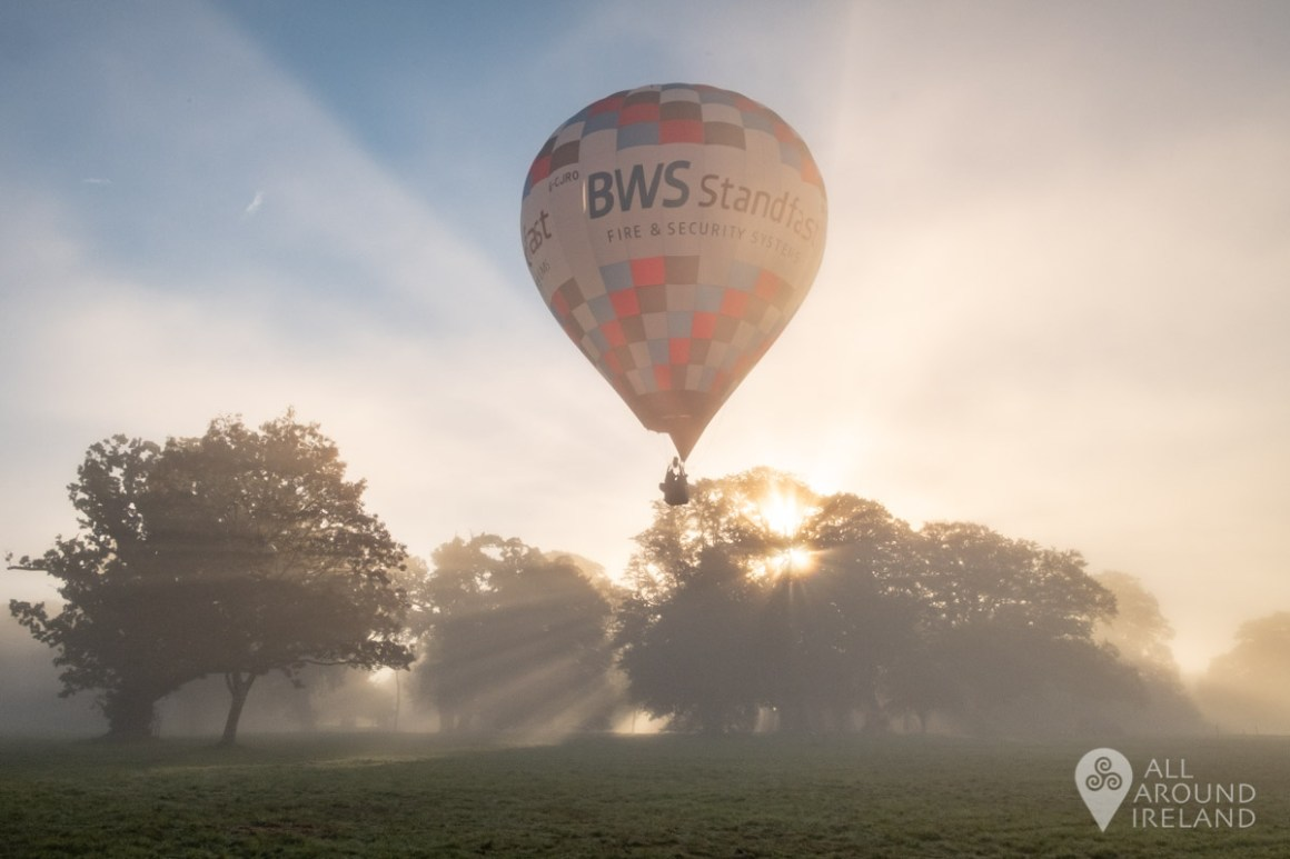 Early morning light disperses through the trees and fog as a hot air balloon passes. Irish Hot Air Ballooning Championships 2018.