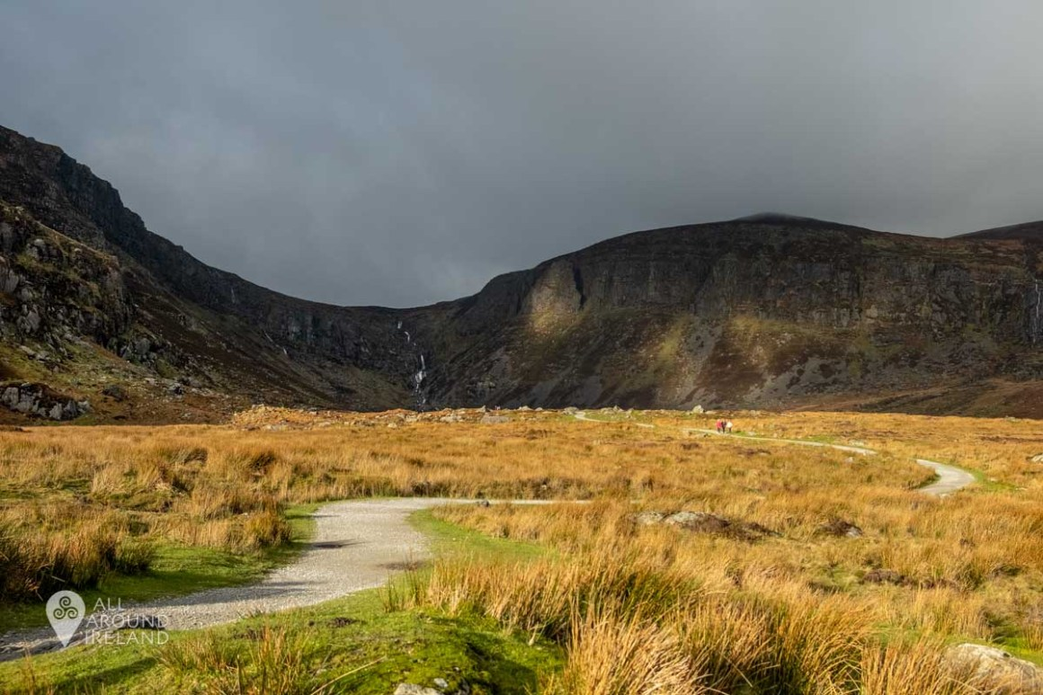 The start of the trail to Mahon Falls. The lighting is dramatic with a dark grey sky and scattered golden light over the hills.