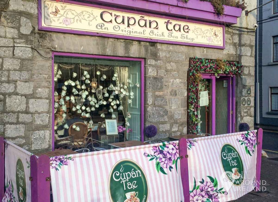 The entrance to Cupan Tae in Galway's Latin Quarter. The door and window frames are purple and china cups hang in the window.