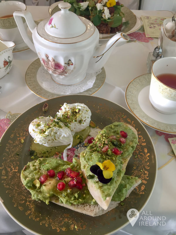 Avocado toast decorated with pomegranate seeds and flowers