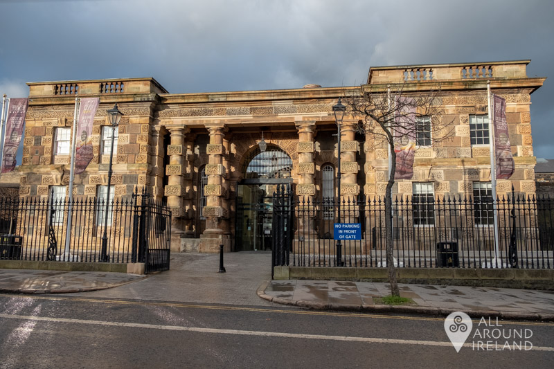 Exterior shot of Crumlin Road Gaol in sunlight with a moody sky in the background