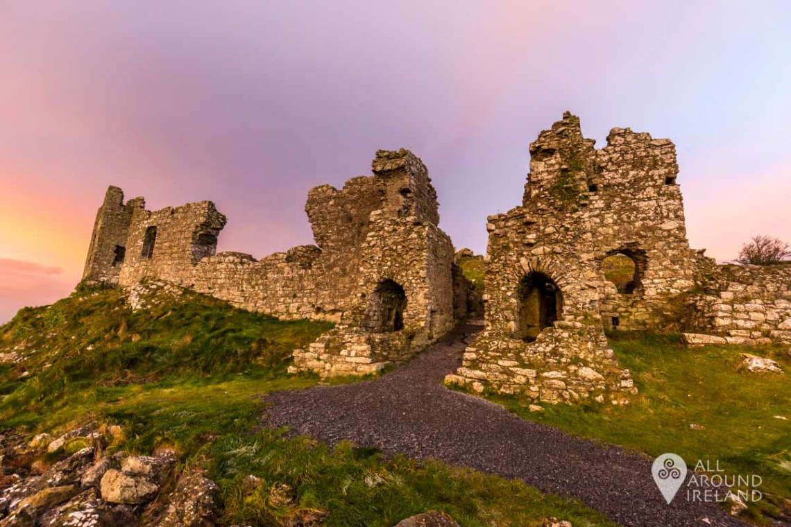 A pink sky at sunrise over the ruins of the main gatehouse of Dunamase Castle