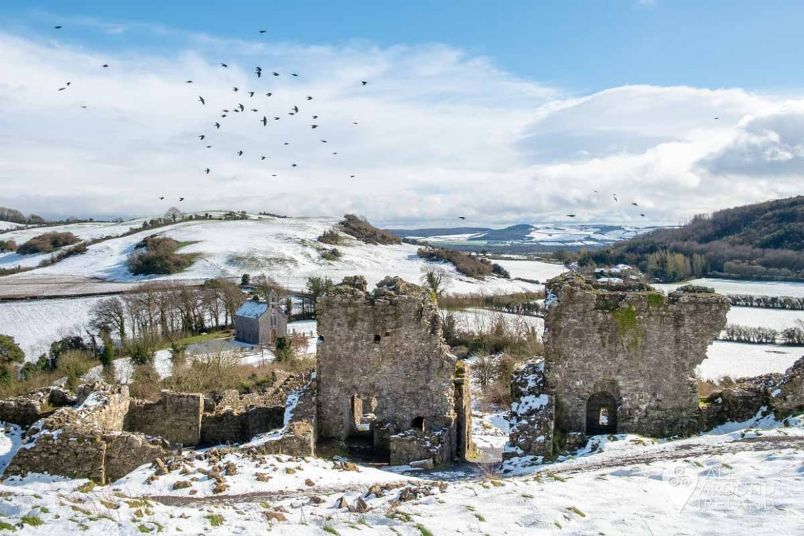 Looking towards the snow covered hills from behind the ruins of the main gatehouse and curtain wall. A large group of birds are flying past overhead.