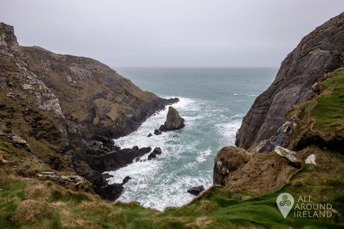 Looking down from the cliff upon where Dunlough Castle is perched