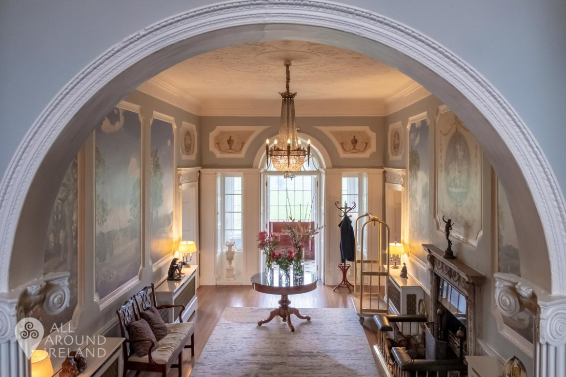 The Manor House hallway with wall murals, chandelier and open fireplace