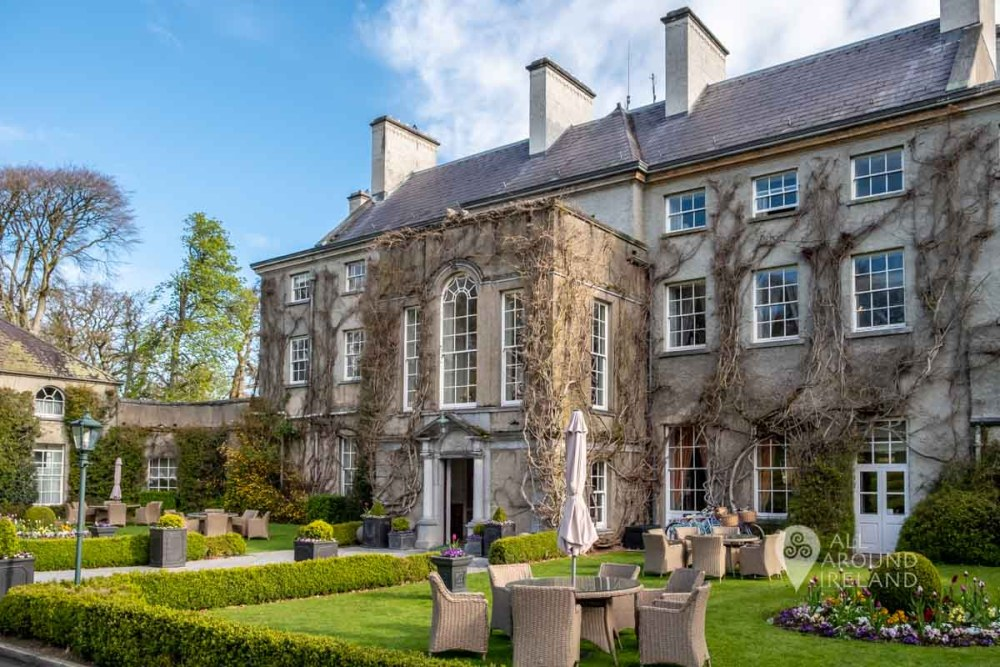 Exterior shot of the Manor House at Mount Juliet with seating on the grassy area in front of the house