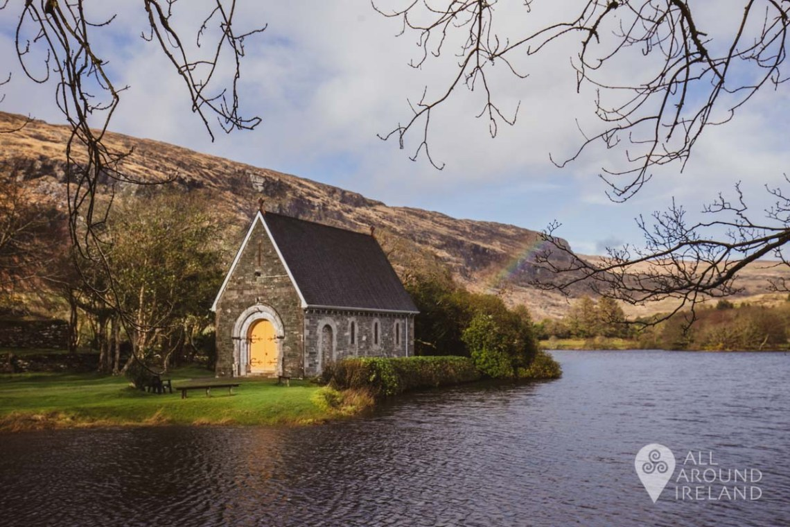 A partial rainbow appears to the right of St Finbarr's Oratory photographed from the lakeshore at Gougane Barra.