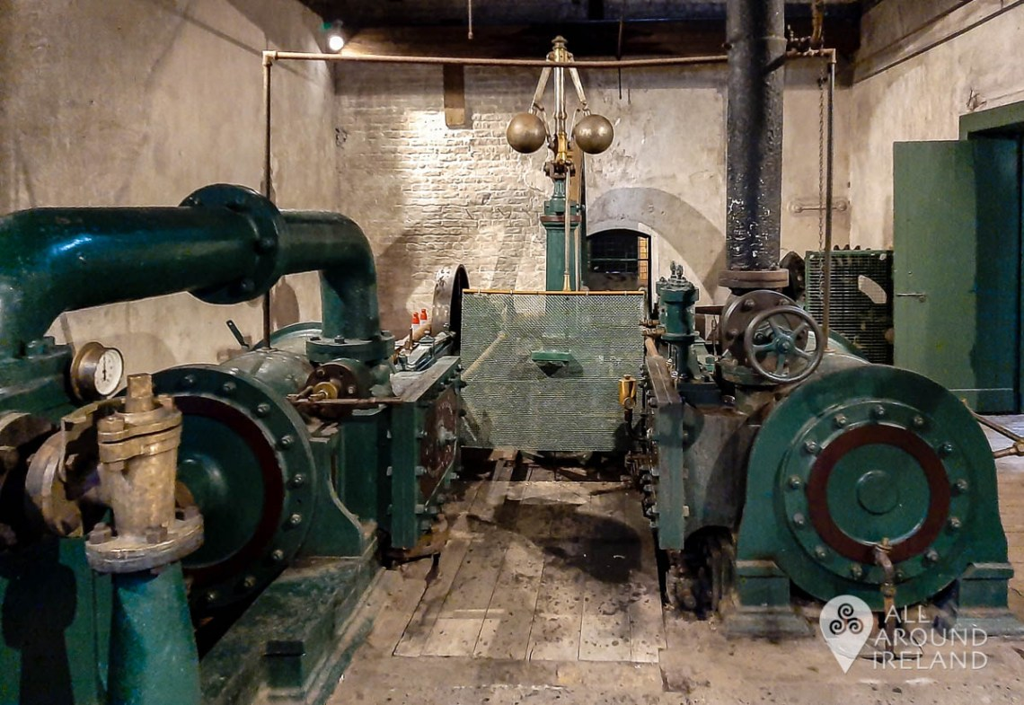 An old pine green steam engine dating from 1887 fills a large room at the Kilbeggan Distillery