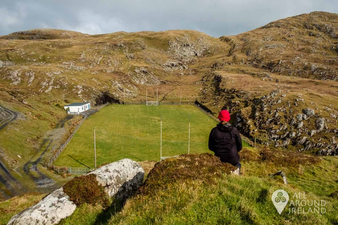 A woman sits on a hilltop looking down on Inishturk GAA Pitch - unique things to do in Ireland