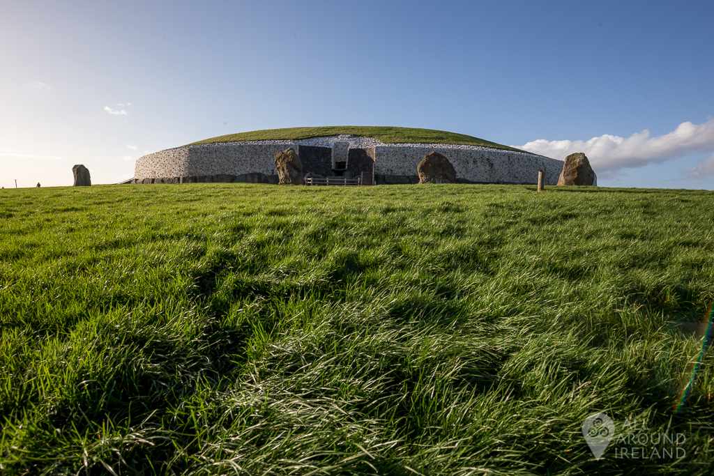 Low angle shot looking towards Newgrange passage tomb with grass moving to the breeze in the foreground - Unique things to do in Ireland