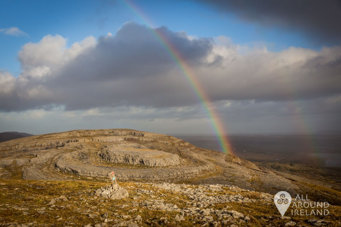 Stormy dark clouds and a rainbow over the rocky landscape of the Burren from the top of Mullaghmore
