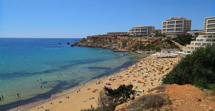Ein Bild des Golden Bay Strand, dem nahen Hotel und dem türkisbluen Meer im Juni.