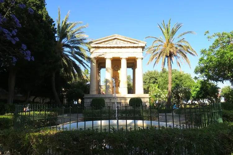 Das Bild zeigt einen im römischen Stil gestalteten Tempel und einen Springbrunnen im mit Palmen und Sträuchern bewachsenen Lower Barrakka Garden in Maltas Hauptstadt Valletta.