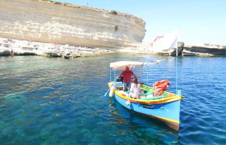 Ein Boot legt am St. Peter´s Pool an. Es ist ein traditionelles maltesisches Luzzu Boot in bunten Farben.