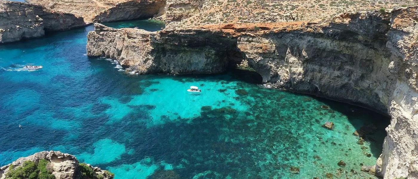 Ein Bild einer Bucht mit türkisblauen Wasser und Klippen auf der zu Malta gehörenden Insel Comino.