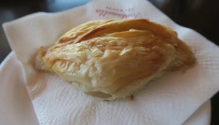 Pastizzi sind kleine, ovale Teigtaschen. Es liegt auf einer Serviette auf einem Teller.