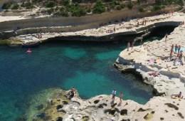 Blick auf den St. Peters Pool auf Malta von den nahen Klippen. Man sieht das türkisblaue Meer, den natürlichen Steinpool und viele Badegäste am St. Peters Pool.